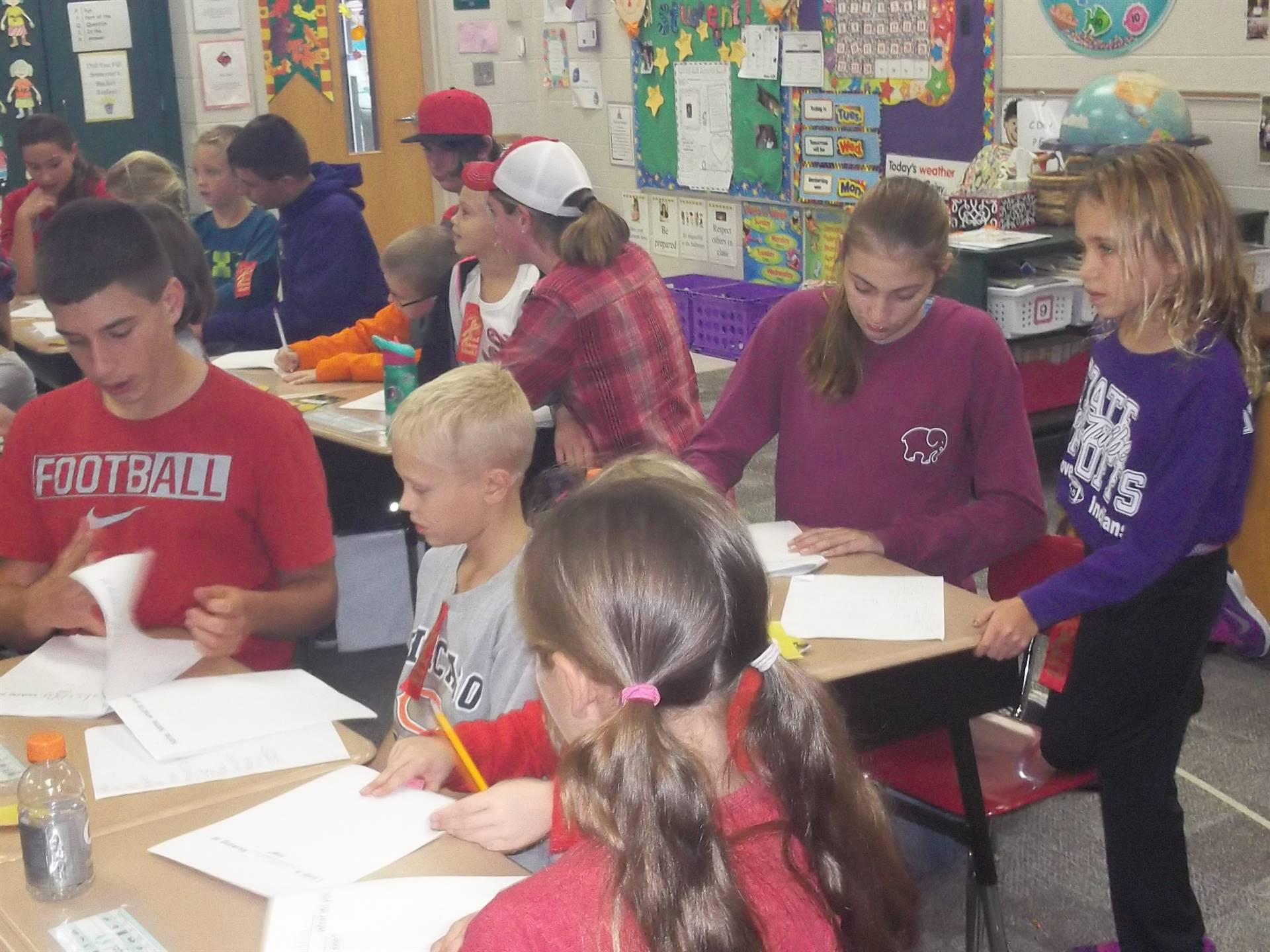 8th grade students help 2nd graders with their Christmas stories